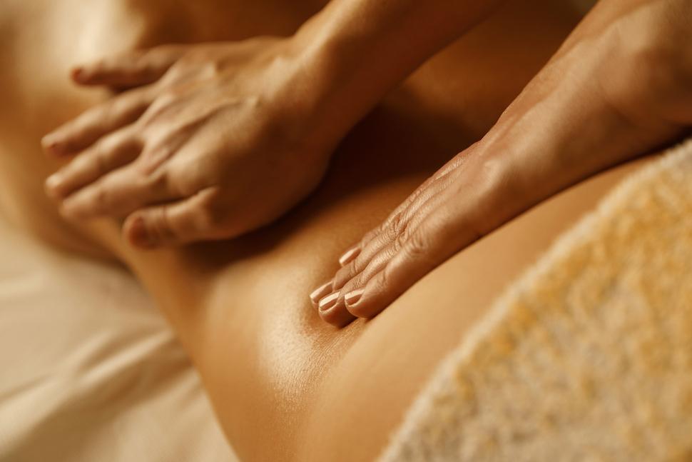 Massage Therapist doing healing massage. Woman enjoying in relaxing massaging at health spa treatment.